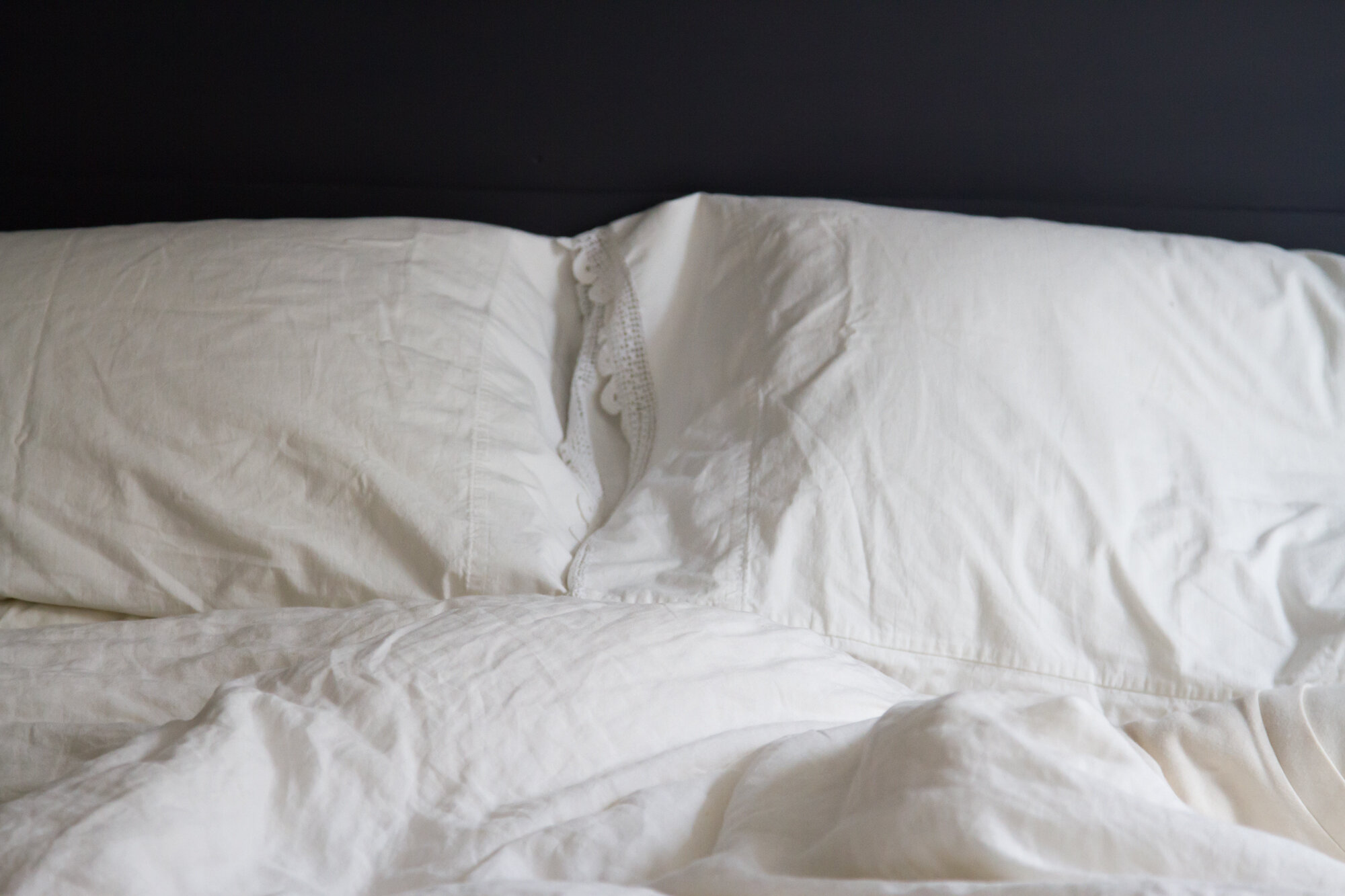 white bed sheets on a blue bed