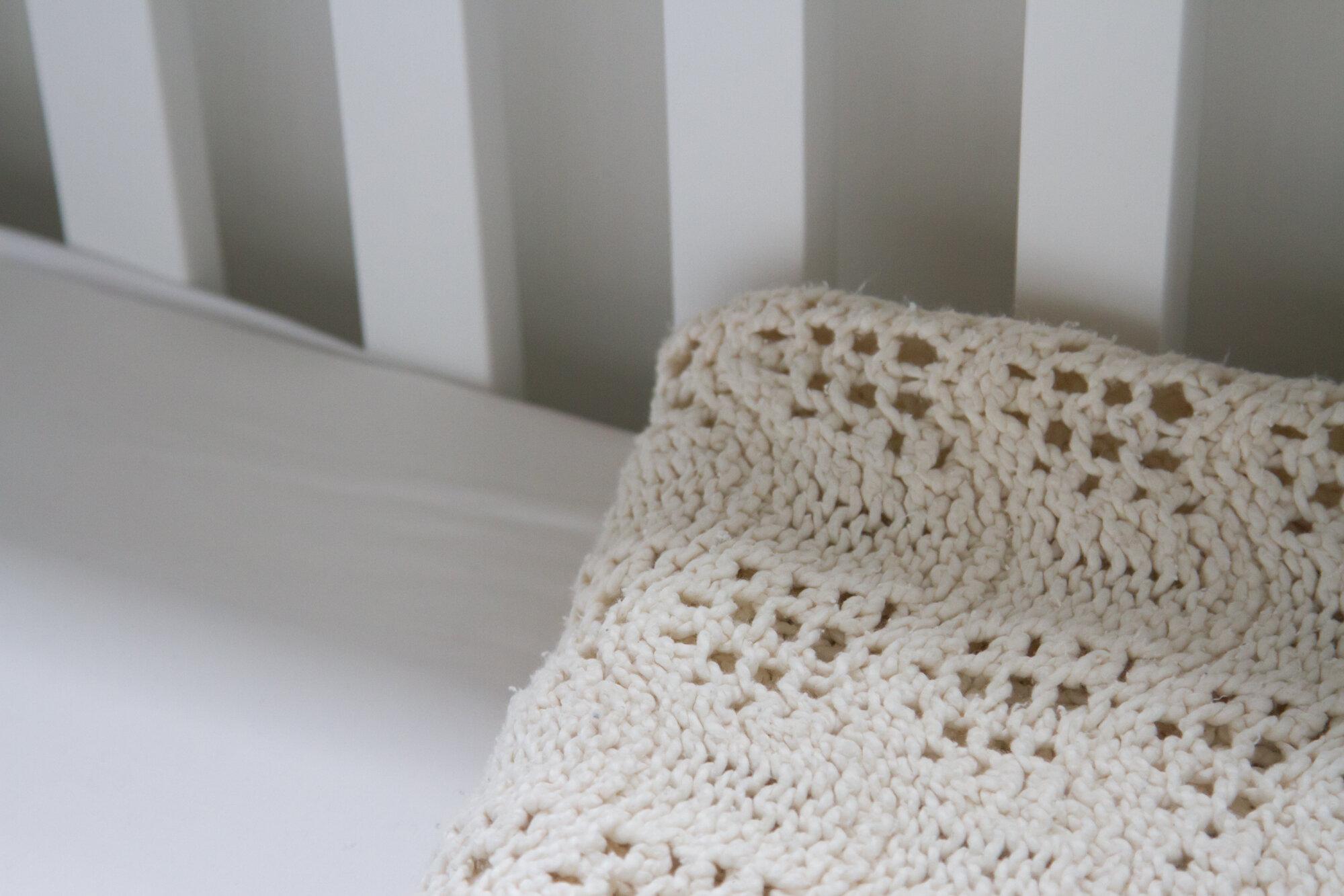handmade off-white blanket in a white crib