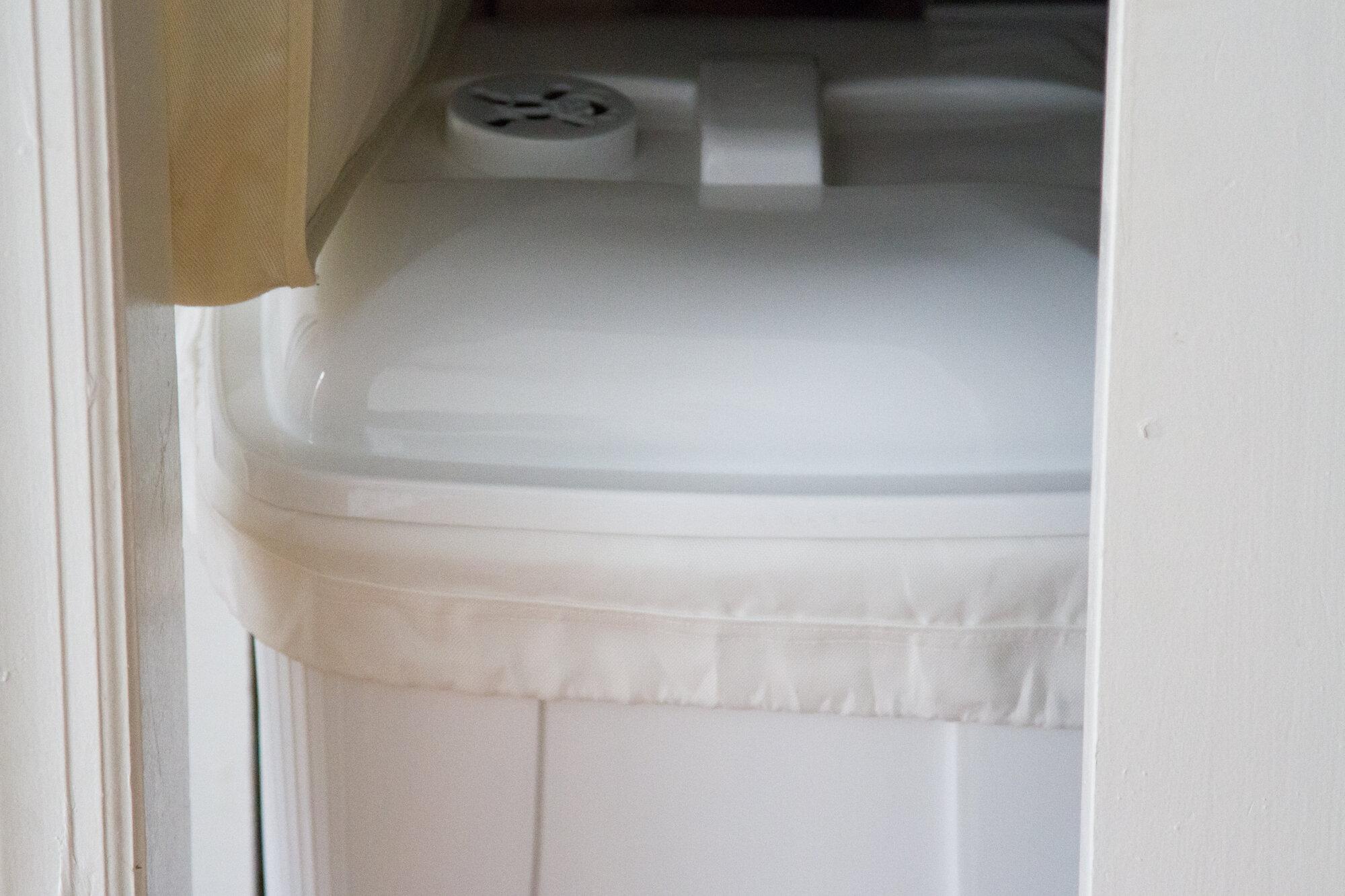 white cloth diaper pail in a closet